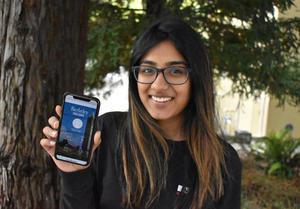 Berkeley student, Sruthi Machina, holds up her iphone showing the Berkeley Fitness Challenge app she worked on.