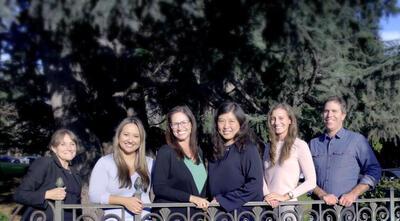 Deborah, Amber, Anissa, Jane, Amy, and Brandon standing behind the University of California sign